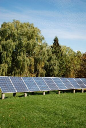 Sun energy batteries on green meadow