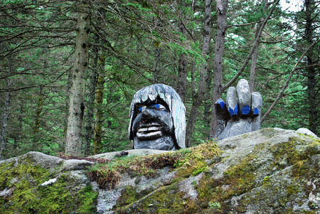 Wooden troll statue behind the rock in Bergen park, Norway Stock Photo