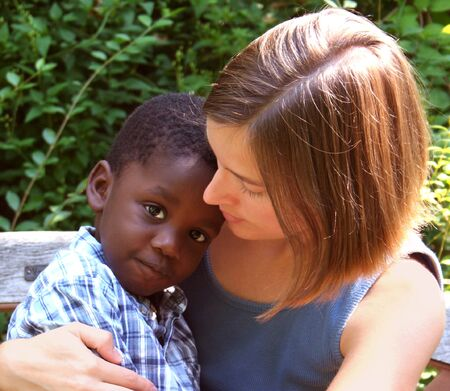 Young Caucasian woman with African American child - Diversity. photo