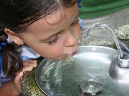 Pretty little girl drinking from a water fountain.