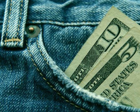 Spending Money - Fifteen American dollars in the pocket of a pair of blue jeans. photo