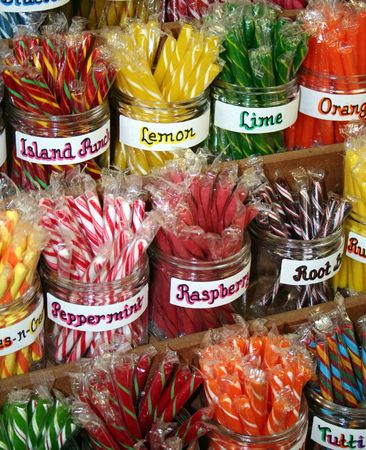 Brightly colored stick candy in clear, glass jars. Stock Photo