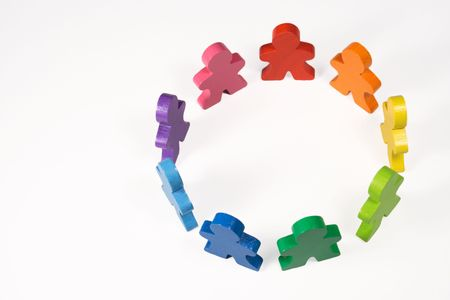Diversity and Teamwork - Brightly colored wooden people standing in a circle. Stock Photo
