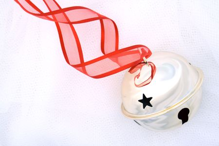 Shiny silver jingle bell with star cut-out on a red ribbon.  White tule background. Stock Photo