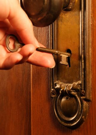 Putting an old-fashioned key into a keyhole photo