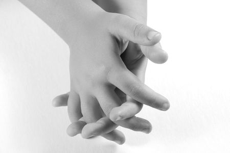 Prayer - a childs hands folded as if in prayer.  Black and white image on white background.