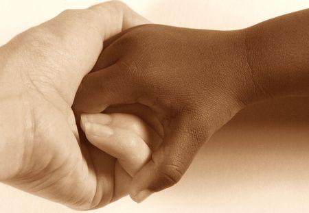 bondad: Diversidad - adulto cauc�sico que lleva a cabo la mano de un ni�o americano africano. Imagen del tono de Sepia en el fondo blanco. Foto de archivo