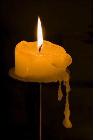 Lit candle with dripping wax on a black background.