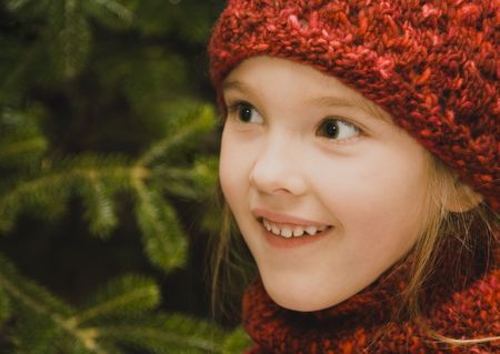 Pretty little girl wearing a red knit hat and matching scarf.
