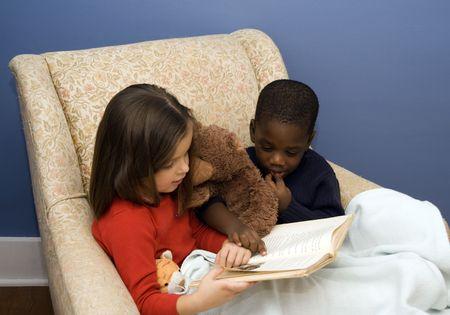 Twee kleine kinderen bij het lezen van een verhaal in een grote, comfortabele stoel. Diversiteit. Stockfoto