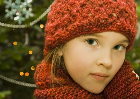 Pretty little girl wearing a red knit hat and matching scarf standing in front of a decorated Christmas Tree. Stock Photo