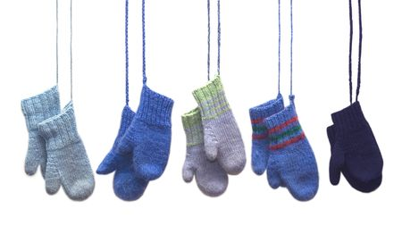 Five pairs of mittens hanging on strings.