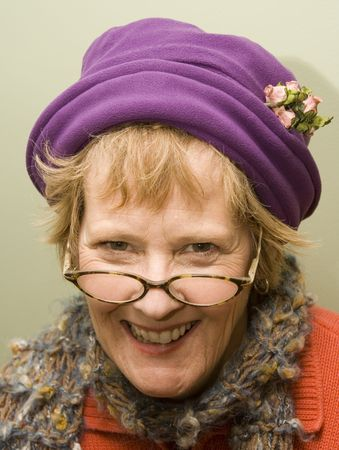 Beauitful older woman wearing a purple hat and red sweater.