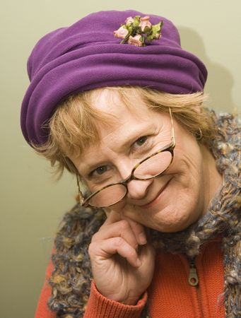 sitter: Beauitful older woman with a fun expression wearing a purple hat and red sweater.
