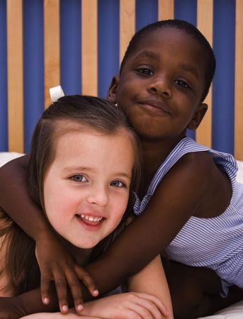 A young African American child hugs a Caucasian girl. Stok Fotoğraf