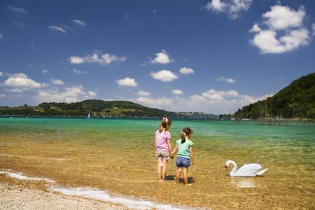 Two young girls standing on the beach watching a swan under a brilliant sky.  Lac du Paladu - France.