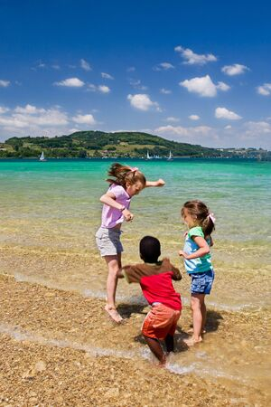 Three small children jumping up and down in the crystal clear water of the Lac du Paladu in France.