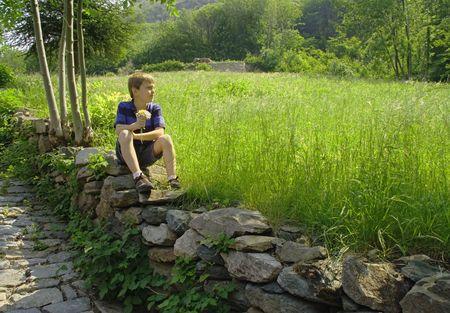 Jongen zit op een stenen muur met een boeket van wilde bloemen. Stockfoto