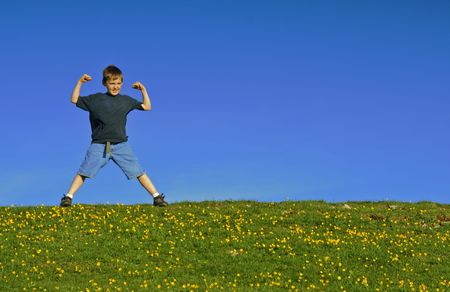 Young boy flexing his muscles on a hill against a blue sky.