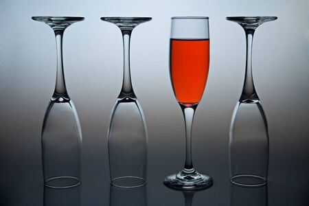 Wineglasses with colored liquid illustrating the concept of possitive thinking. Stock Photo