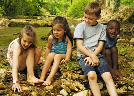 Four small children on rocks in the water.