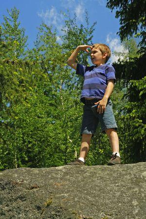 太陽に対して彼の目をシェーディングと探しているボールダーに立っている若い男の子