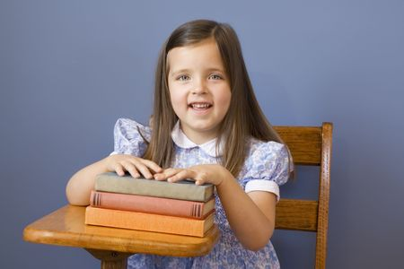 Little girl sitting at a wooden school desk. photo