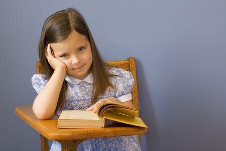Little girl sitting at a wooden school desk.