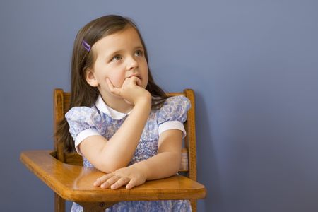 Little girl sitting at a wooden school desk.