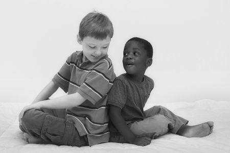 racisme: Twee jonge jongens van verschillende rassen spelen samen. Stockfoto