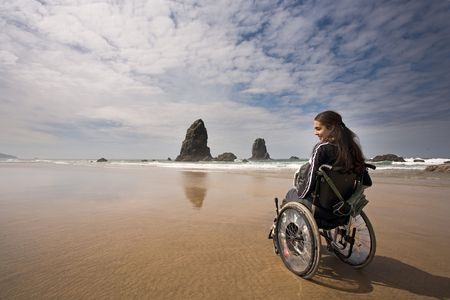 wheel chair: Beautiful young woman in a wheel chair visiting Beach in Oregon, USA. Stock Photo