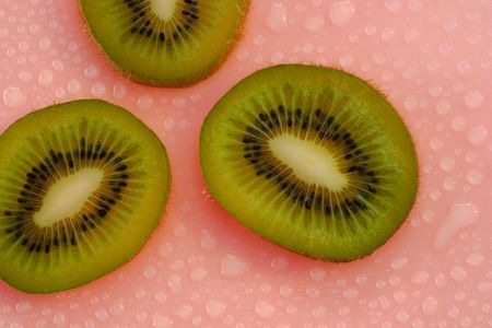 Fresh kiwi and water droplets on a red background - delicious and nutritious. Stock Photo - 809205
