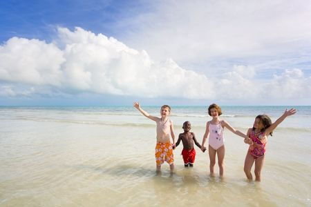 Four young children of diferent races playing in the water at the beach. Bahia Honda, Florida Keys.