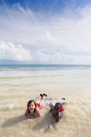 Two young children - an African American boy and a Caucasian girl - playing in the water at the beach. Bahia Honda, Florida Keys.