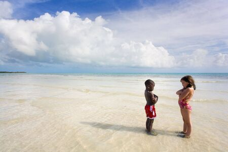 Two young children - an African American boy and a Caucasian girl - glaring at each other in the water at the beach. Bahia Honda, Florida Keys. Stock Photo