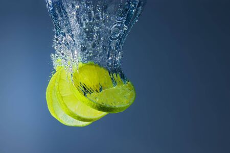 Fresh lime slices falling into water. A delicious and nutritious snack. Standard-Bild