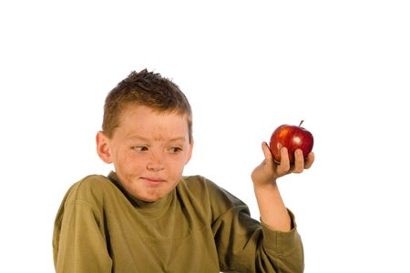 Very dirty young boy holding an apple and looking embarrased. Studio shot isolated on a white background. Stock Photo
