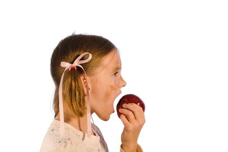Very dirty young girl taking a bite from an apple. Studio shot isolated on a white background.
