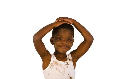 Very dirty African American boy smiling at the camera with his arms above his head. Studio shot isolated on a white background.