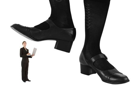 tailored: Giant feet preparing to crush a female business professional wearing tailored suit and holding a laptop computer. Conceptual image isolated on a white background. Stock Photo