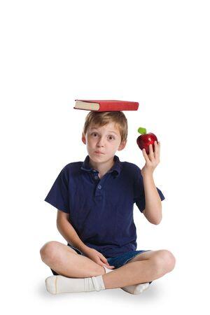illiteracy: Un joven, ni�o de raza cauc�sica la celebraci�n de una manzana en su mano y un libro rojo sobre su cabeza. Esta imagen forma parte de una serie de im�genes conceptuales aisladas en blanco or�genes.  Foto de archivo