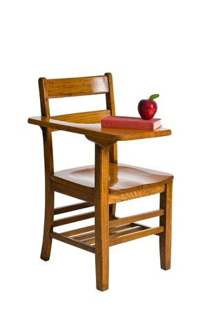 A wooden school desk with a red book and an apple. This image is isolated on a white background. Stock Photo