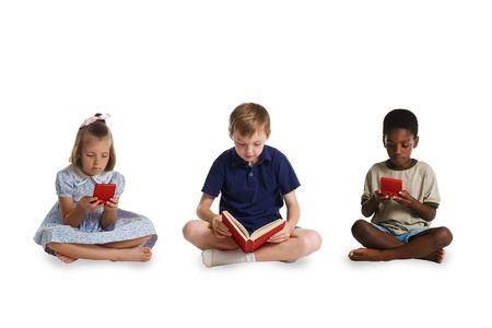 illiteracy: Los ni�os peque�os de diferentes razas sentados juntos - dos jugando juegos electr�nicos y la tercera lectura de un libro. Esta imagen es parte de una serie de im�genes conceptuales aislados sobre fondos blancos.