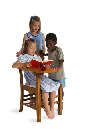 illiteracy: Tres ni�os peque�os de diferentes razas de lectura junto a un mostrador de madera de la escuela. Aislado en un blanco.  Foto de archivo