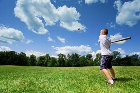 Young Caucasian boy playing baseball in a sunny field on a beautiful summer day. Stock Photo