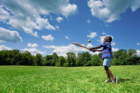 Little African American boy playing baseball in a sunny field on a beautiful summer day. Stock Photo