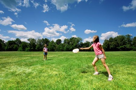 Two little girls playing with a flying disc in a sunny field on a beautiful summer day.