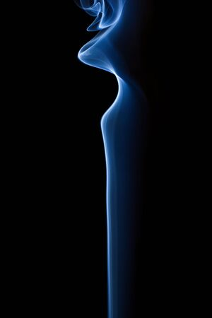 Beautiful patterns in soft, blue smoke as it rises into the air. Isolated on Black. Stock Photo