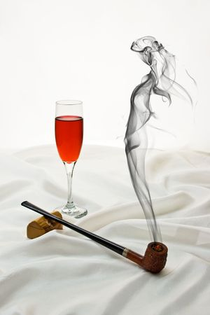 to tempt: Wooden pipe and wine glass on satin with drifting smoke in the shape of a beautiful woman.