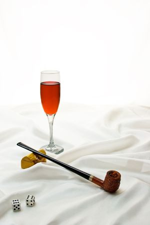 Wooden pipe, dice and wine glass on satin with copy space. Stock Photo